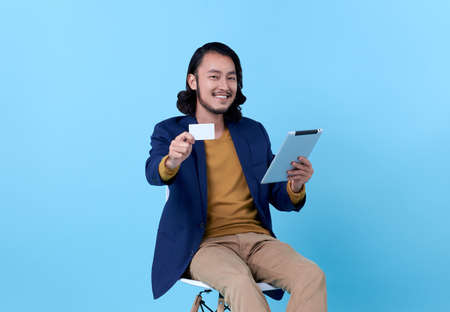 Business man asian happy smiling showing credit card and using a digital tablet while sitting on chair isolated on bright blue background.