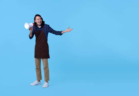 Entrepreneur handsome asian man shouting into megaphone isolated on blue background.