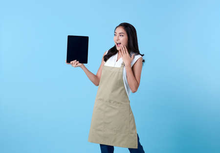 Entrepreneur asian woman using tablet computer on blue background.