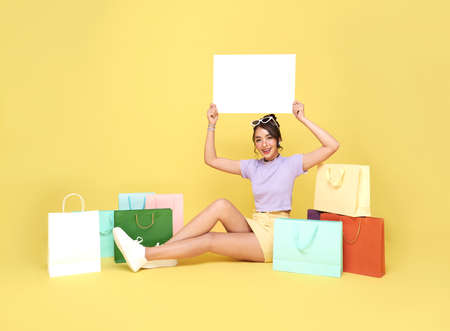 Beautiful teen Asian woman shopper sitting with shopping bags and holding blank banner in hands on yellow background.