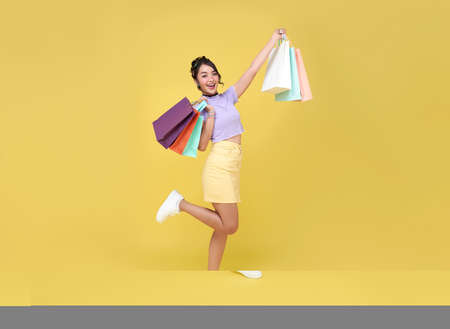 Cheerful happy teen asian woman enjoying shopping, she is carrying shopping bags to get the latest offers at the shopping center.