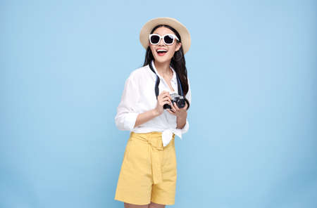 Happy Asian woman dressed in summer clothes holding photo camera and looking away isolated over blue background.