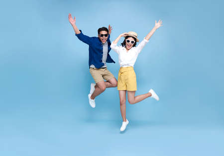 Happy Asian couple tourist jumping celebrating to travel on summer holiday isolated on blue background. Фото со стока