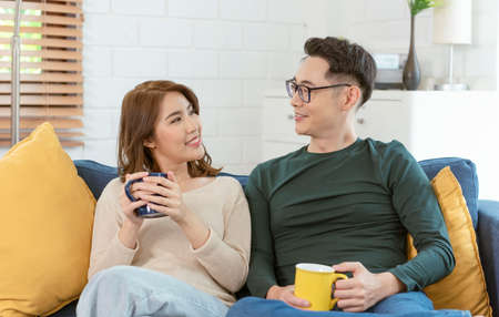 Asian couple man and woman drinking coffee together on sofa in living room at home. family lifestyle concept.