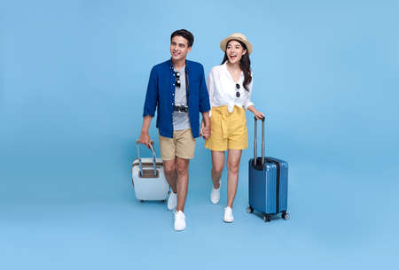 Happy Asian couple tourist with luggage enjoying their summer vacation getaway together isolated on blue background.