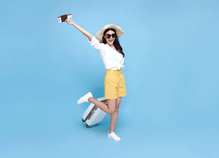 Happy smiling Asian woman dressed in summer clothes with passport and luggage enjoying their summer vacation getaway in blue background.