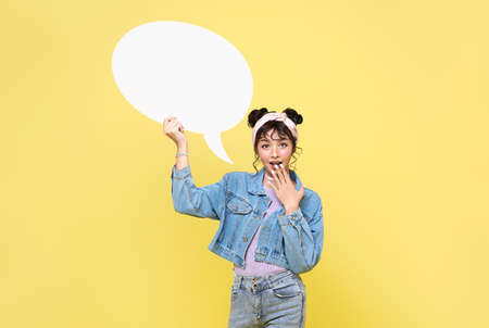Excited Asian teen girl holding blank speech bubbles on yellow background. Фото со стока
