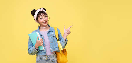 Happy Asian girl with backpack holding books and pointing finger on blank space beside over yellow background. back to school concept. Фото со стока