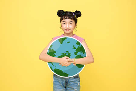 Happy Asian cute girl schoolgirl hug globe isolated on yellow background. World environment day concept. Фото со стока