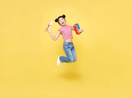 Happy Asian child girl jumping up with diploma and book isolated on yellow background.