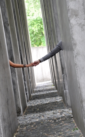 labyrinthine: Couple with hands clasped into a labyrinthine gray pillars.
