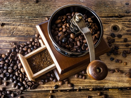 Wooden coffee grinder with ground coffee, on a wooden background