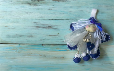 Christmas fairy on a blue old wooden background, blue rag fairy