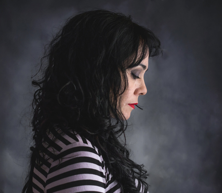 Brunette woman in profile with striped shirt and gray background
