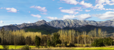 Panoramic landscape of mountains with trees and blue sky. Panoramic view of the Sierra de Gredos, Spain