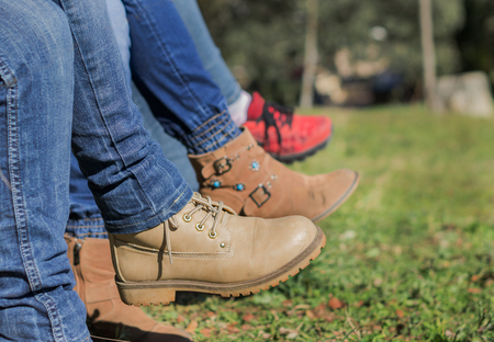 Woman legs crossed with cowboy pants and boots in the field