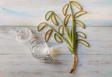 Natural aloe vera gel in glass jar with aloe vera plant, top view