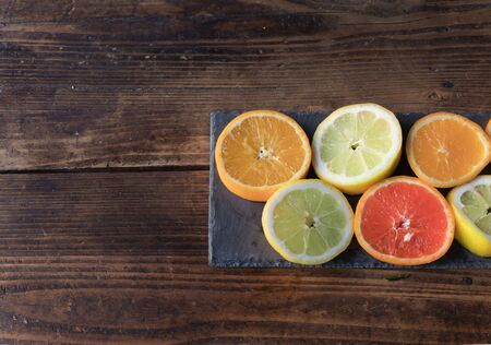 Sliced lemons and oranges cut on a slate board, on a wooden table