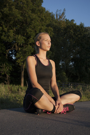 cross legged: beautiful young woman is doing breathing exercises sitting cross legged after running outdoors