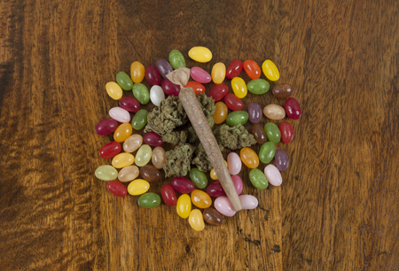 Jellybeans and Cannabis sativa, prepared for munchies while smoking weed joint Archivio Fotografico