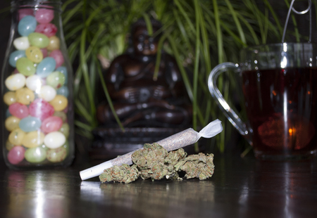 closeup of rolled marijuana weed joint and buds, on wooden background, with Buddha statuette, colorful jellybeans and cup of rooibos tea Stockfoto