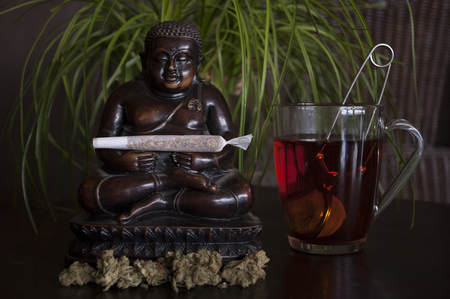 closeup of rolled marijuana weed joint and buds with Buddha statuette and cup of rooibos tea on wooden ground