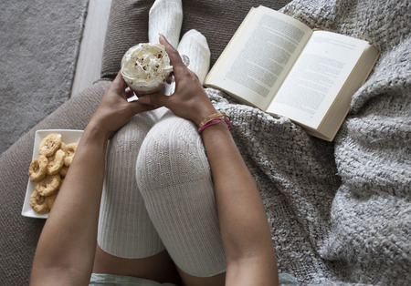 closeup of woman reading book at home on couch with hot chocolatemilk and cookies Stockfoto
