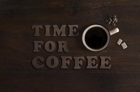 plat leggen van kopje biologische koffie, biologische rietsuiker kubussen en fair trade chocolade bonen, op donkere houten achtergrond Stockfoto