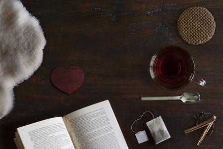 mooie gezellig plat leggen van kopje thee, boek, schapenvacht, koekje en specerijen op rustieke houten grond Stockfoto