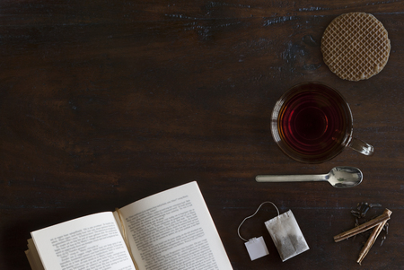 mooie gezellig vlak leggen van kopje thee, boek, koekje en specerijen op rustieke houten grond