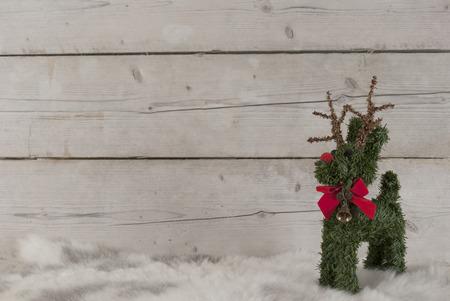 Kerstmisachtergrond, leuk rendier die zich op schapehuid bevinden, op houten achtergrond