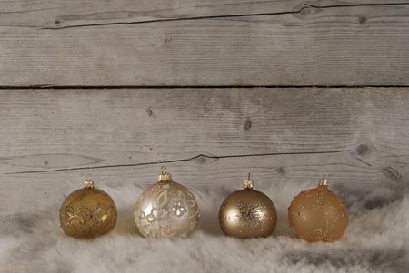 prachtige bronzen en gouden glazen kerstballen, op schapenvacht en verweerde houten achtergrond