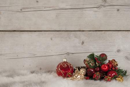 Kerstmisstilleven met rode glassnuisterij en ornamenten op schapehuid en oude houten achtergrond Stockfoto