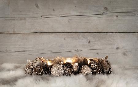 Klassieke gouden theelichthouder van Kerstmis met brandende kaarsen, op schapenvacht en doorstane houten achtergrond Stockfoto