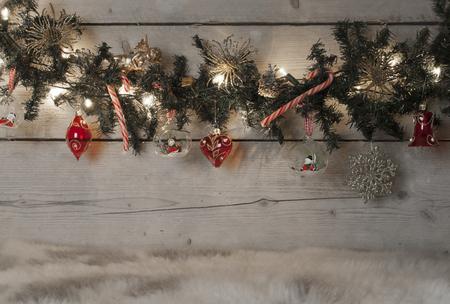 Christmas pine tree garland met rode ballen, snoep stokken en ornamenten, opknoping op oude houten bord staande op schapenvacht