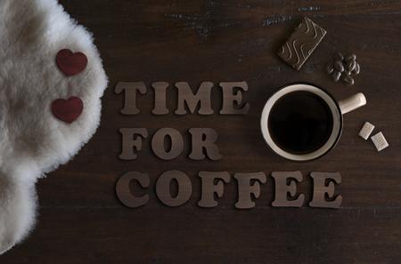 mooie plat leggen van mok met koffie, schapenvacht, chocolade en tekst tijd voor koffie, op rustieke houten achtergrond Stockfoto