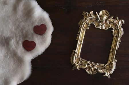 Antiq gouden fotolijst in Rococo-stijl, op donkere rustieke houten achtergrond met witte Toscaanse schapenvacht en harten Stockfoto - 93634978