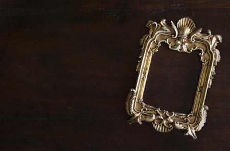 antiq gouden fotolijst in Rococo-stijl, op donkere rustieke houten achtergrond