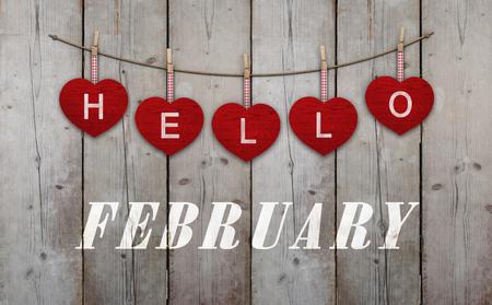 Hallo februari geschreven op hangende harten en verweerde houten achtergrond Stockfoto - 94658297