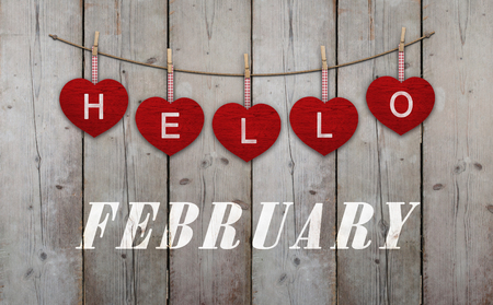 Hello february written on hangingred hearts and weathered wooden background Stockfoto