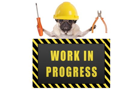 pug dog wearing yellow constructor safety helmet,holding pliers and screwdriver, with warning sign saying work in progress, isolated on white background Stockfoto