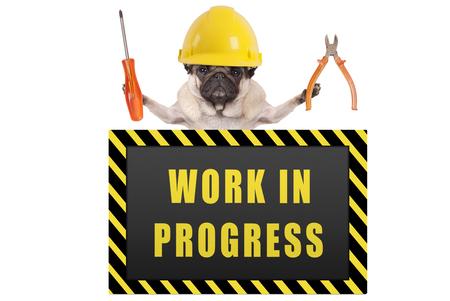 Pug hond dragen gele constructor veiligheidshelm, met een tang en schroevendraaier, met waarschuwingsbord zeggen werk in uitvoering, geïsoleerd op witte achtergrond Stockfoto - 94424573