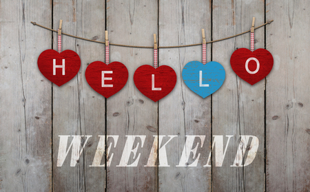 Hello weekend written on hanging red and blue wooden  hearts, on background of used weathered scaffolding wood Stockfoto