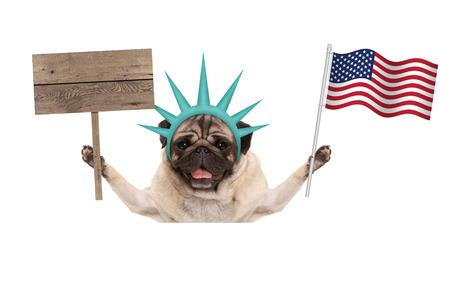 lachende pug puppy hond bedrijf Amerikaanse vlag en lege houten bord, het dragen van dame Liberty kroon, geïsoleerd op een witte achtergrond Stockfoto