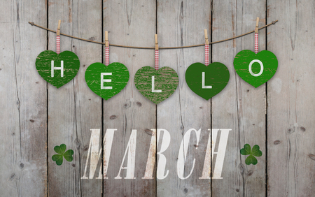 Hello March written on hanging green hearts and weathered wooden background, with clover Stockfoto