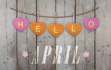 Hello April written on hanging pink and orange hearts and weathered wooden background, with flowers Stockfoto