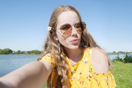 beautiful young millennial girl, taking selfie pcture with cell phone camera, outdoors in park on sunny day Stockfoto - 101847899