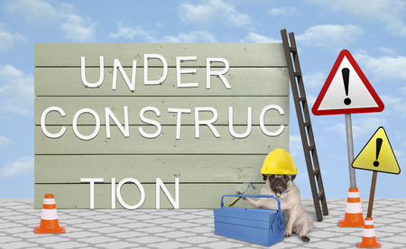 cute repairman pug puppy dog with yellow safety helmet, sitting down next to wooden board sign, with text under construction Archivio Fotografico