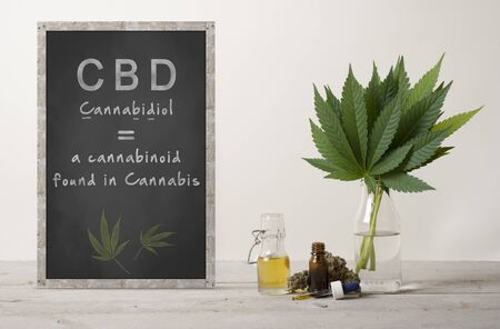 rustic blackboard with text cannabidiol and marujuana cannabis sativa weed leaves bouquet, flower bud and CBD oil in glass dropper bottle, on wooden countertop Archivio Fotografico