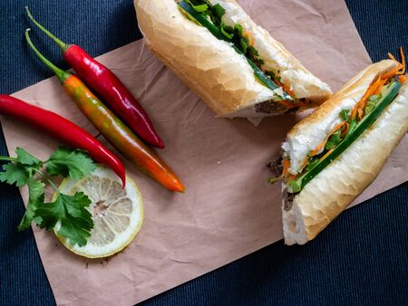 Banh mi bo from Vietnam with lemon, peppers and coriander on a piece of paper